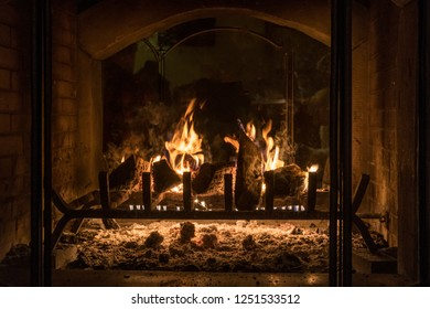 Wood burning fireplace with grate, logs and flame
