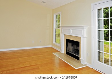 Wood burning fireplace in a room with oak floors flanked by a window and a french door.