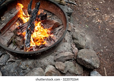 Wood burns in a campfire ring at a campsite.