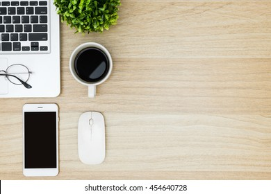 Wood business office desk table with laptop, smartphone with black blank mockup screen, cup of coffee and supplies. Top view with copy space, flat lay.