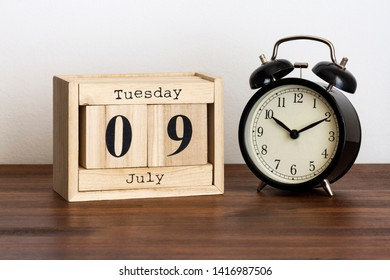 Wood calendar with date and old clock. Tuesday 9 July