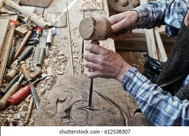 Wood carving. Carver with chisel and hammer. A skillful craftsman working on a panel of wood carve decoration
