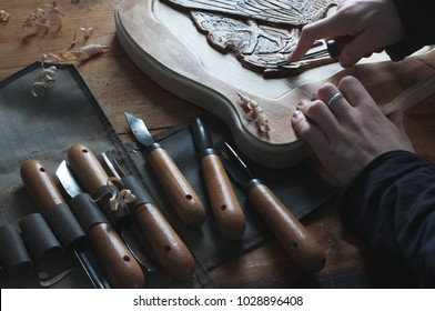 Wood carving, craftsman's hands cut out the bas-relief, master of carving