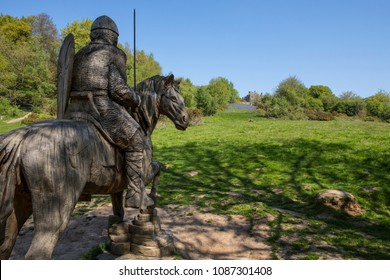 A wood carving of a Norman soldier on horseback looking towards Battle Abbey in East Sussex, UK.  The fields at Battle Abbey are where the Battle of Hastings took place in 1066.