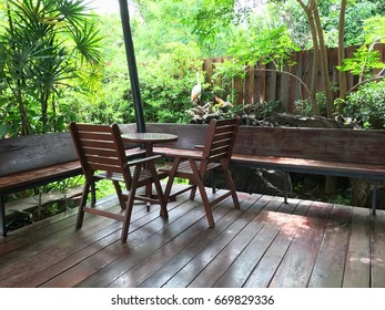 Wood chairs and table with garden background