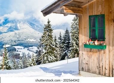 Wood chalet with typical Austrian decoration over scenery of sow mountains.
