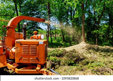 Wood Chipper in Action captures a wood chipper or mulcher shooting chips over a fence.