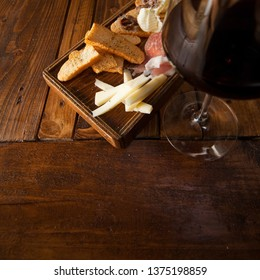 Wood chipping with cheese, bread, butter, fishes, ham; red wine glass on rustic table. With space for your text or logo.