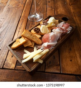 Wood chipping with cheese, bread, butter, fishes, ham; red wine glass on rustic table