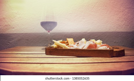 Wood chipping with cheese, bread, butter, fishes, ham; red wine glass on rustic table. Selective focus, vintage effect and space for your text or logo.