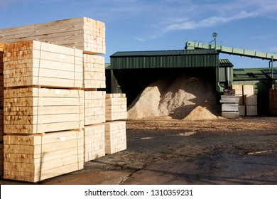 Wood chips pellets chopped wooden logs and stacked wooden pallets for biomass fuel at sawmill