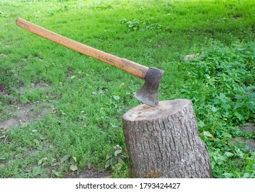 The wood chopper sticks out in wooden hemp. Ax and ax handle. Woodworking. Deforestation by a sharp axe. Ax to chop wood. Rusty but very sharp forester's ax or carpenter's axe