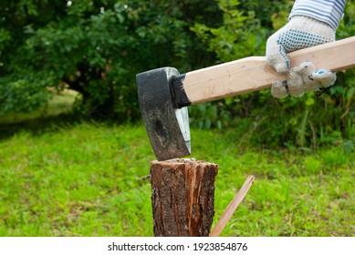 Wood chopping at backyard. Man's hand holding axe preparing to chop a log. Outdoors. Copyspace. Summer.