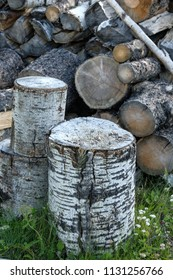 A wood chopping block with split wood in a pile behind
