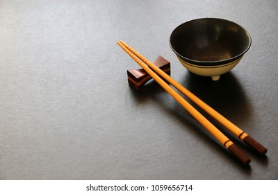 wood chopsticks and ceramic bowl on black table background