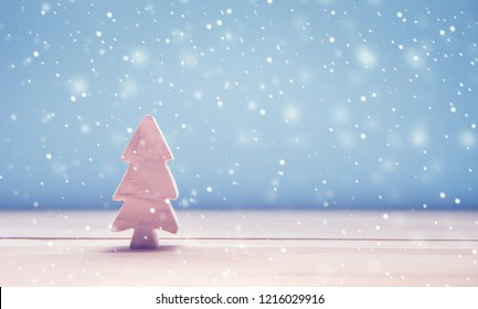 Wood christmas tree on table with blue pastel color background, copy space, minimal idea concept.