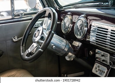 Wood and chrome. Steering wheel and dashboard of a retro car . Salzburg, Austria - 16 November 2019