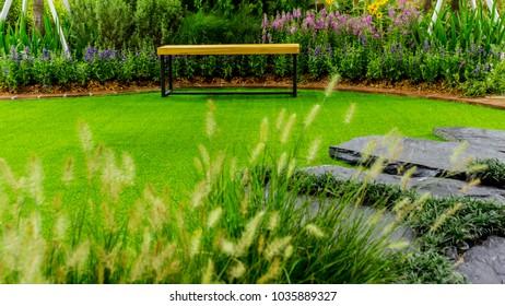 Wood couch in flower cozy garden.