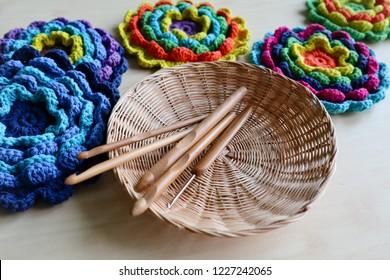 Wood crochet needles and Flowers crochet appliqué on beige wood background.