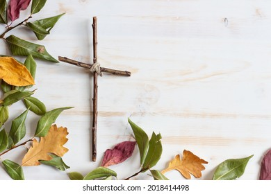Wood cross with autumn leaf border on white wood background  - Shutterstock ID 2018414498