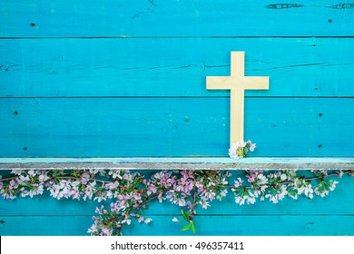 Wood cross hanging on antique rustic wooden background over white and pink spring flowers; Easter, religious and spiritual background with teal blue copy space