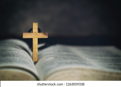 Wood Cross Sign Symbol and Praying to God with a Bible in the Morning Devotion.