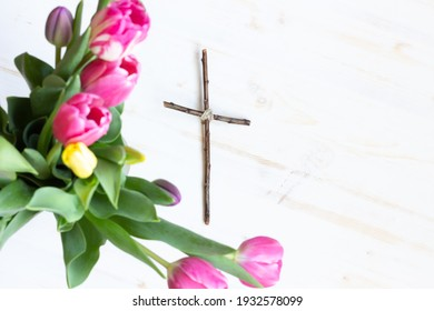 Wood cross with tulips and white wood background