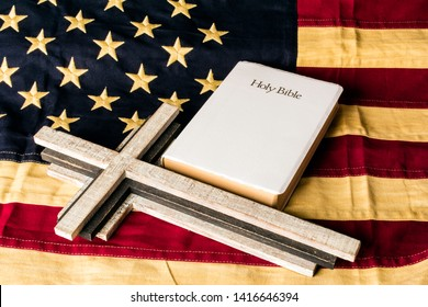 wood cross and white bible on tea stained cotton american flag
