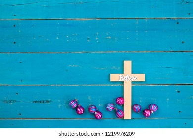 Wood cross with the word Believe hanging on antique rustic teal blue wooden background with colorful turquoise and pink Christmas ornaments;  religious holiday and spiritual background with copy space