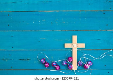 Wood cross with the word Faith hanging on antique rustic teal blue wooden background with colorful turquoise and pink Christmas ornaments;  religious holiday and spiritual background with copy space