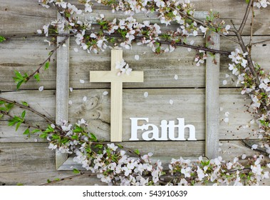 Wood cross and the word Faith hanging on on antique rustic wooden background with white and pink flowers border; Easter holiday background with spring tree blossoms and copy space