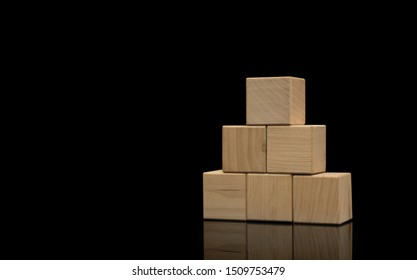 Wood cube arrange in pyramid shape on black background, business concept. Wooden blocks stacked in the shape of a pyramid.