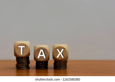 Wood cube tax and coin money stack on wooden table background. Tax Day 2019 takes place on April 15 copy space