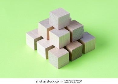 Wood cubes or blocks arranged in geometrical pattern on green background