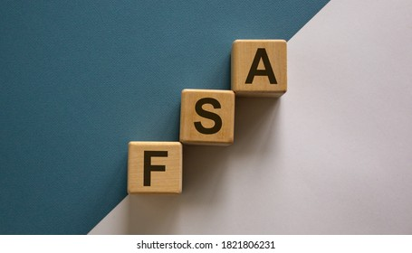 Wood cubes with word 'FSA, flexible spending account' stacking as step stair on paper blue and white background, copy space. Business concept. - Shutterstock ID 1821806231