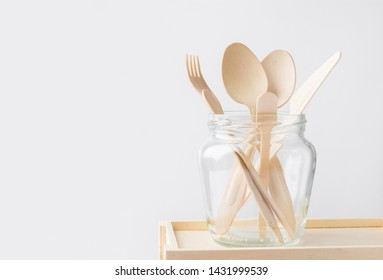 Wood cutlery spoons fork knife in a glass jar on white wall background. Zero waste plastic free reusable biodegradable eco friendly materials. Sustainability concept. Minimalist poster with copy space