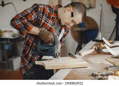 Wood cutting with circular saw. Closeup of mature man sawing lumber.