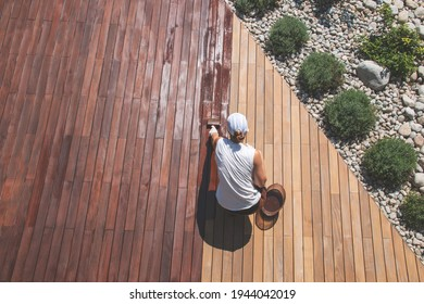 Wood deck renovation treatment, the person applying protective wood stain with a brush, overhead view of ipe hardwood decking restoration process