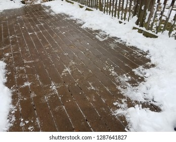 wood deck with snow and ice partially removed