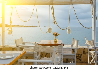 wood deck of traditional Greek cafe in front of beach landscape with sea view.