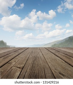 Wood deck as a tranquil old rustic country patio floor in perspective with a summer sky on a beautiful mountain range with forest trees as a symbol of travel and backyard living.
