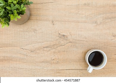 Wood desk table with a cup of coffee and a green plant. Top view with copy space, flat lay. Minimal concept.