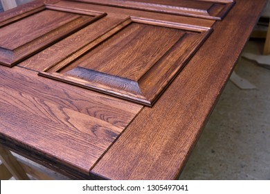 Wood door manufacturing process. Door leaf, painted in dark color. Woodworking and carpentry production. Furniture manufacture. Close-up