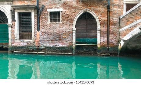 Wood door and window. On redbrick wall, building facade in Venice, exterior design