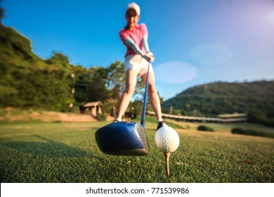 wood driver and golf ball in Addressing the ball by woman golf player, ready to hit away from tees off to fairway ahead