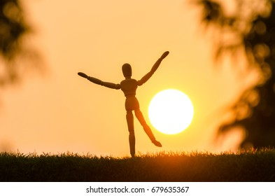 wood dummy raise hand in morning day with sunrise. wooden dummy represents success in business target. happy and start the next day.