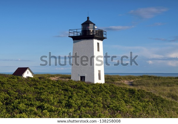 Wood End lighthouse overlooking harbor amid beach shrubbery on a late summer day in Provincetown, Massachusetts.