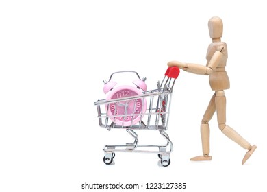 A wood figure Mannequin pushing a shopping card with a clock isolated on white