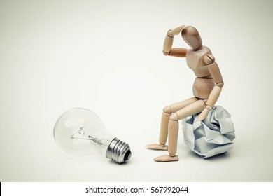 Wood figure mannequins sitting on a crumpled paper ball watching an incandescent light bulb / Business success and failure concept
