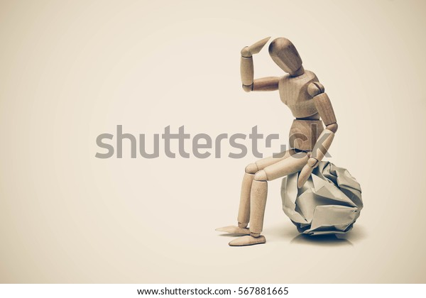 Wood figure mannequins sitting on a crumpled paper ball / Having no idea concept